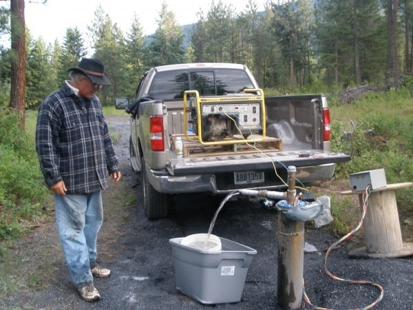 man standing with generator on a pickup truck